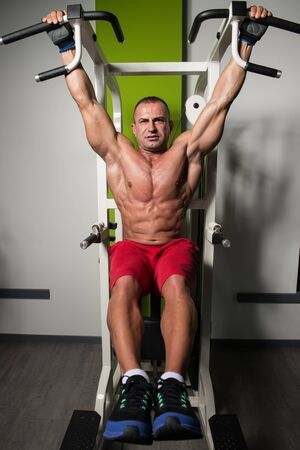 Mature Man Performing Hanging Leg Raises Exercise - One Of The Most Effective Ab Exercises Stock Photo