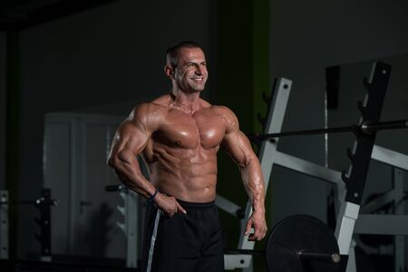 Healthy Mature Man Standing Strong In The Gym And Flexing Muscles - Muscular Athletic Bodybuilder Fitness Male Posing After Exercises