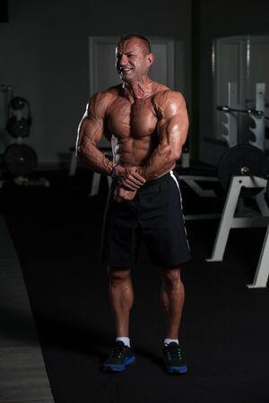 Porträt eines reifen, körperlich fitten Mannes, der seinen gut trainierten Körper zeigt - muskulöser athletischer Bodybuilder Fitness-Mann, der nach Übungen posiert Standard-Bild