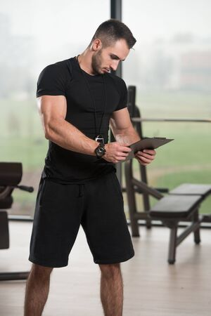 Personal Trainer Takes Notes On Clipboard In Fitness Center Gym