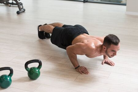 Healthy Man Athlete Doing Pushups Workout With Kettle Bell In A Gym - Kettle-bell Exercise