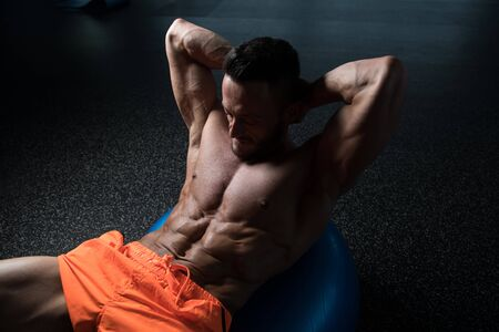 Muscular Young  Man Exercising Abdominals On Exercise Ball In Modern Fitness Center