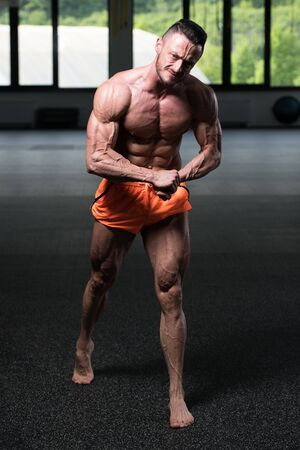 Young Man Standing Strong In The Gym And Flexing Muscles - Muscular Athletic Bodybuilder Fitness Model Posing After Exercises Stockfoto