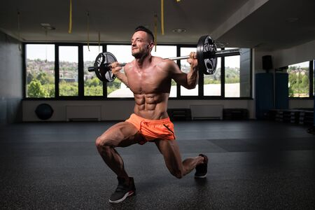 Strong Man In The Gym Exercising Legs With Barbell - Muscular Athletic Bodybuilder Fitness Model Exercise