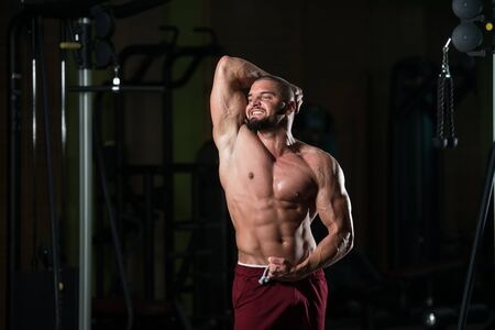 Handsome Young Man Standing Strong In The Gym And Flexing Muscles - Muscular Athletic Bodybuilder Fitness Model Posing After Exercises 版權商用圖片