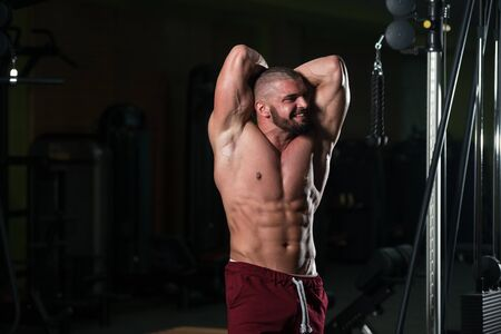 Healthy Young Man Standing Strong In The Gym And Flexing Muscles - Muscular Athletic Bodybuilder Fitness Model Posing After Exercises
