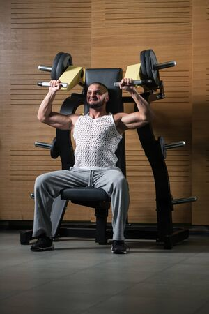 Handsome Muscular Fitness Bodybuilder Doing Heavy Weight Exercise For Shoulders On Machine With Cable In The Gym Stock Photo - 135462089