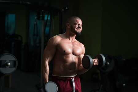 Man Working Out Biceps In A Gym - Dumbbell Concentration Curls