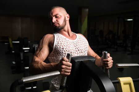 Handsome Athlete Doing Heavy Weight Exercise For Back On Machine 版權商用圖片