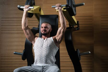 Handsome Muscular Fitness Bodybuilder Doing Heavy Weight Exercise For Shoulders On Machine With Cable In The Gym Stock Photo - 135462317