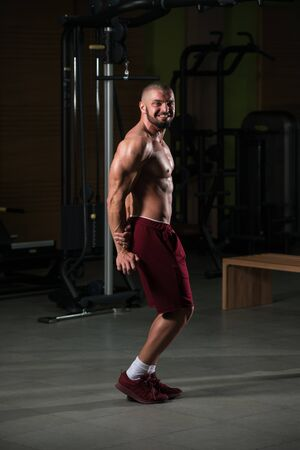 Healthy Young Man Standing Strong In The Gym And Flexing Muscles - Muscular Athletic Bodybuilder Fitness Model Posing After Exercises Imagens - 135459792