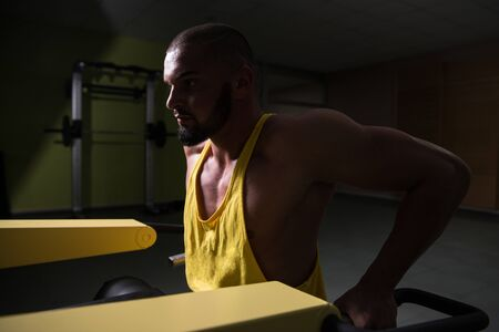 Man Doing Heavy Weight Exercise For Trapezius On Machine 版權商用圖片