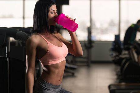 Attractive Women Resting After Exercise And Drinking From Shaker Imagens