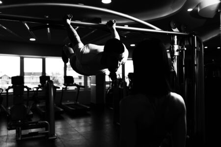 Personal Trainer Showing Young Woman How To Train Pull Ups - Chin-Ups In The Gym