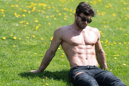 Healthy Young Man Lying Down Strong Flexing Muscles While Wearing Black Jeans - Muscular Athletic Bodybuilder Fitness Model Posing Outdoors - a Place for Your Text Imagens