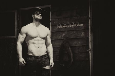 Handsome Cowboy Man Standing Strong Posing at Ranch Outdoors Wearing Black Jeans and Cowboy Hat