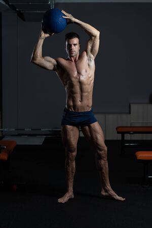 Portrait Of A Young Physically Fit Man Showing His Well Trained Body With Medicine Ball - Muscular Athletic Bodybuilder Fitness Model Posing After Exercises