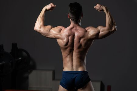 Handsome Young Man Standing Strong In The Gym And Flexing Muscles - Muscular Athletic Bodybuilder Fitness Model Posing After Exercises Imagens - 139808024