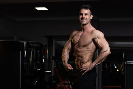 Handsome Young Man Standing Strong In The Gym And Flexing Muscles - Muscular Athletic Bodybuilder Fitness Model Posing After Exercises Imagens