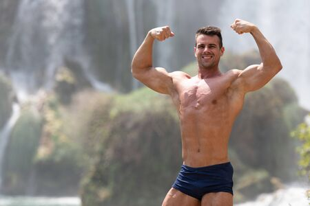 Portrait Of A Young Physically Fit Man Showing His Well Trained Body in Front of Waterfall