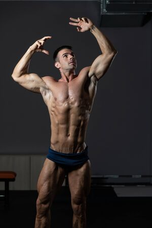 Portrait Of A Young Physically Fit Man Showing His Well Trained Body - Muscular Athletic Bodybuilder Fitness Model Posing After Exercises 写真素材