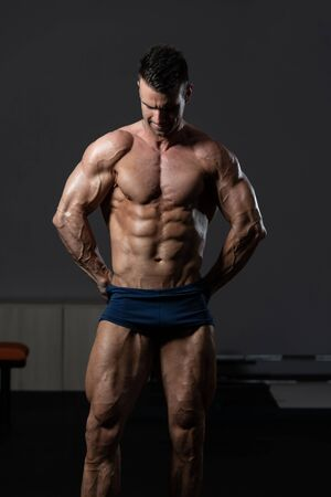 Young Man Standing Strong In The Gym And Flexing Muscles - Muscular Athletic Bodybuilder Fitness Model Posing After Exercises Reklamní fotografie