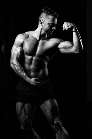 Young Man Standing Strong In The Gym And Flexing Muscles - Muscular Athletic Bodybuilder Fitness Model Posing After Exercises Imagens - 140449763