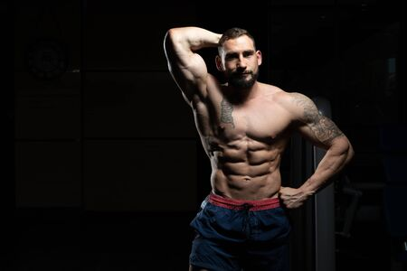 Young Man Standing Strong In The Gym And Flexing Muscles - Muscular Athletic Bodybuilder Fitness Model Posing After Exercises Imagens - 140599337