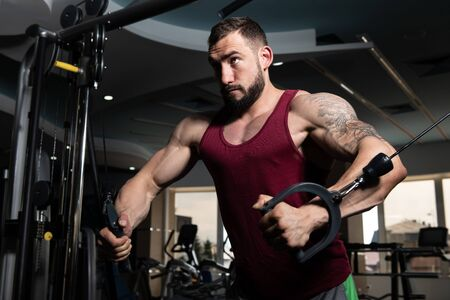 Handsome Muscular Fitness Bodybuilder Doing Heavy Weight Exercise For Chest On Machine With Cable In The Gym Foto de archivo