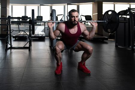 Man Working Out Legs With Barbell In A Gym - Squat Exercise