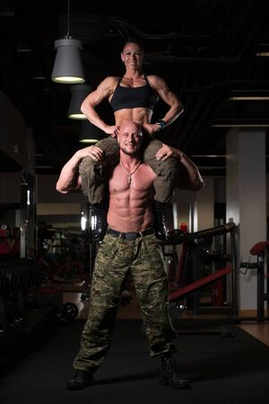 Fitness Couple Standing Strong In The Gym And Flexing Muscles - Muscular Athletic Woman Sitting on Bodybuilder and Posing After Exercises