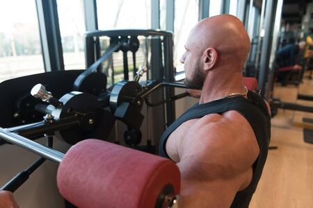 Muscular Fitness Bodybuilder Doing Heavy Weight Exercise For Shoulders On Machine With Cable In The Gym Stock Photo