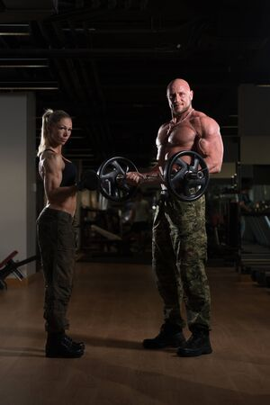 Strong Young Couple Working Out With Dumbbells And Barbell For Biceps In The Gym With Exercise Equipment