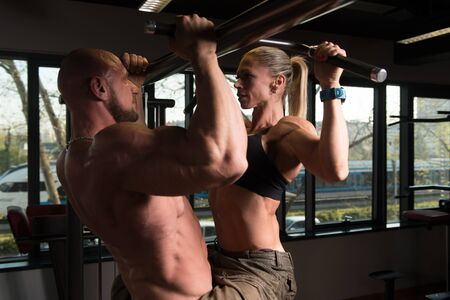 Strong Young Couple Working Out Doing Pull Ups - Chin-Ups For Back In The Gym