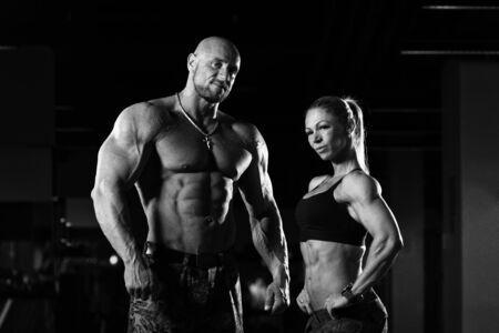 Fitness Couple Standing Strong In The Gym And Flexing Muscles - Muscular Athletic Bodybuilder Model Posing After Exercises Stock Photo