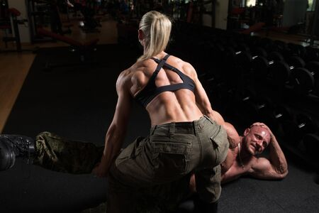 Sporty Fit Woman Picking Up Partner From Floor In The Gym - Exercise For Back