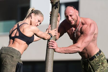 Strong Young Couple Working Out Outdoors In Park With Tree