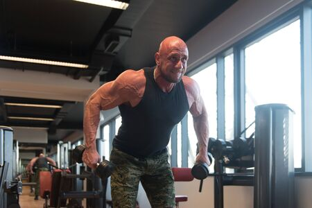 Man Working Out Shoulders With Dumbbells in a Gym