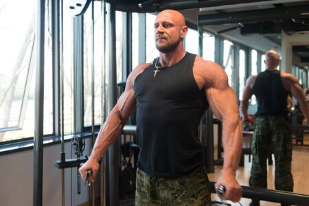Muscular Fitness Bodybuilder Doing Heavy Weight Exercise For Shoulders On Cable Machine In The Gym