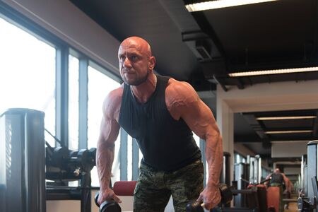 Athlete Working Out Shoulders With Dumbbells in a Gym