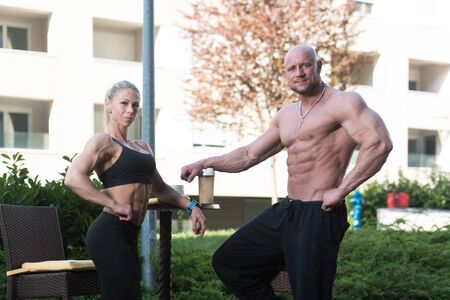 Handsome Good Looking And Attractive Couple With Muscular Body Relaxing Outdoors and Drinking Water From Shaker Stock Photo