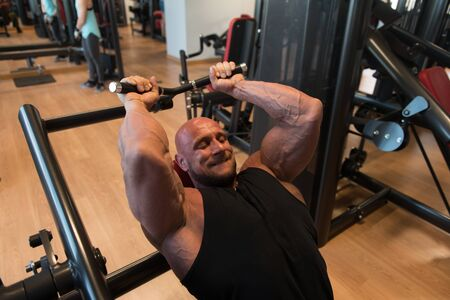 Muscular Fitness Bodybuilder Doing Heavy Weight Exercise For Triceps On Machine With Cable In The Gym