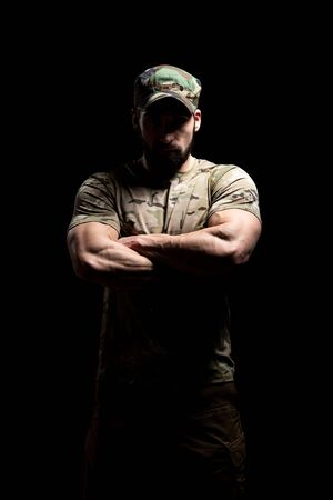 Portrait of a American Marine Corps Special Operations Modern Warfare Soldier Arms Crossed With Cap on Black Background