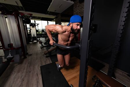 Muscular Fitness Bodybuilder Doing Heavy Weight Exercise For Triceps And Chest on Parallel Bars In The Gym Imagens - 147216947
