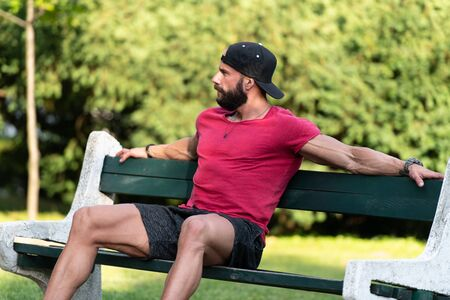 Smiling Athlete Sitting and Resting on Benchin a Park Doing Some Jogging Outdoors