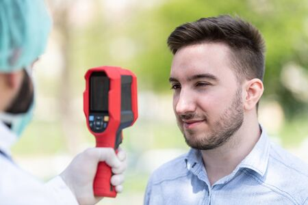 Doctor Man Use Infrared Forehead Thermometer Gun to Check Body Temperature for Virus Covid-19 Symptoms With the Isolation Gown or Protective Suits and Surgical Face Masks Outdoors in Park Foto de archivo