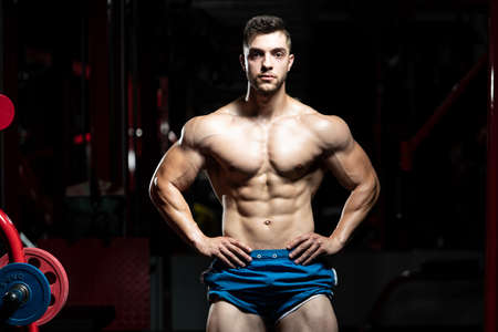 Young Man Standing Strong In The Gym And Flexing Muscles - Muscular Athletic Bodybuilder Fitness Model Posing After Exercises Banco de Imagens