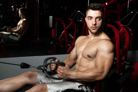 Handsome Athlete Doing Heavy Weight Exercise For Back On Machine Banco de Imagens