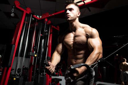 Handsome Muscular Fitness Bodybuilder Doing Heavy Weight Exercise For Chest On Machine With Cable In The Gym