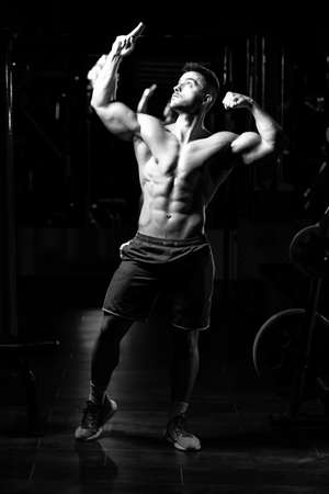 Handsome Man Standing Strong In The Gym And Flexing Muscles - Muscular Athletic Bodybuilder Fitness Model Posing After Exercises Banco de Imagens